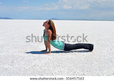 Young woman stretching and performing yoga on the Bonneville Salt Flats in Utah. - stock photo
