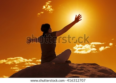 young woman stretching arms sitting on a rock at sunset - stock photo