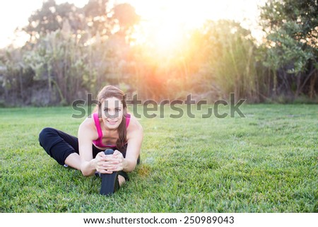 Young woman stretching at the park at sunset - stock photo
