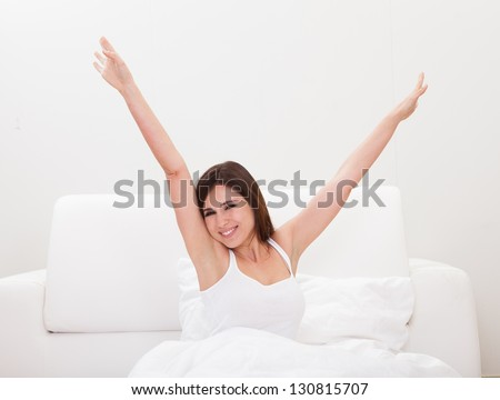 Young Woman Stretching Her Arms In Bed - stock photo