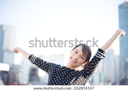 young woman stretching her arms on the roof - stock photo