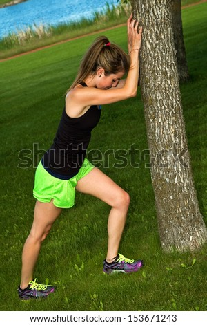 Young woman stretching her calf muscle, against a tree in a city park. - stock photo