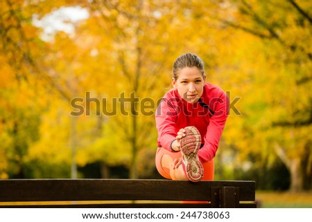 Young woman stretching her leg on bench before jogging in autumn nature - stock photo