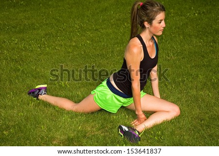 Young woman stretching her legs. - stock photo