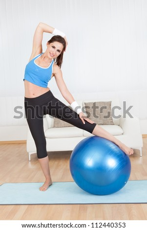 Young woman stretching her muscles at home - stock photo