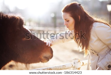 Young woman stroking pony in mini zoo, love and affection - stock photo