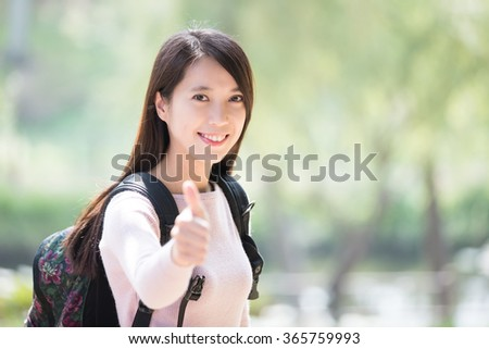 young woman student smile to you and show thumb up gesture. nature green background, asian beauty - stock photo