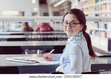 young woman student studying and looking in book and writing down in the library - stock photo