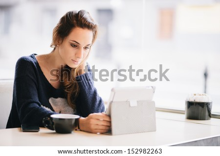 Young woman / student using tablet computer in cafe - stock photo