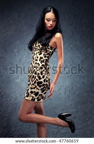 Young woman studio fashion. On wall background. - stock photo
