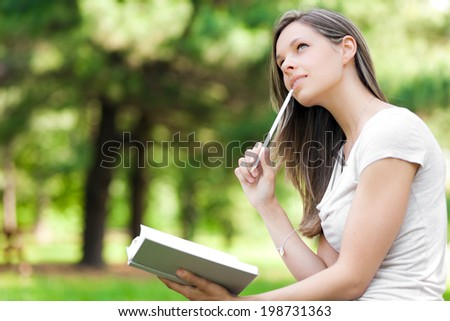 Young woman studying at the park - stock photo