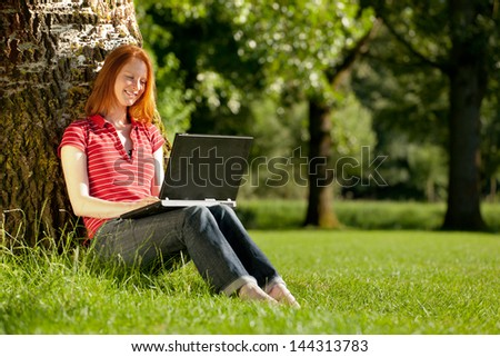 Young woman studying with a laptop outdoors in sunny weather. - stock photo