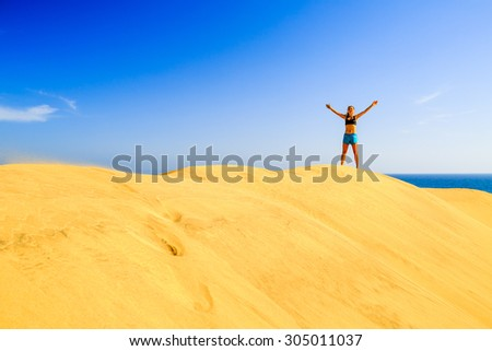 Young woman success business concept on beautiful inspirational beach dunes on sunny summer day. Beauty female runner jogging and exercising, success motivation and inspiration outdoors in nature - stock photo
