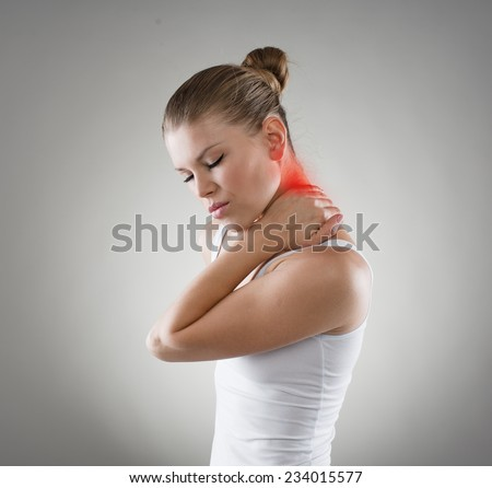 Young woman suffering from neck cramp. Nape pain and treatment concept. - stock photo