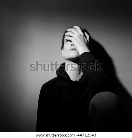Young woman suffering from severe depression/anxiety  (B&W image) - stock photo