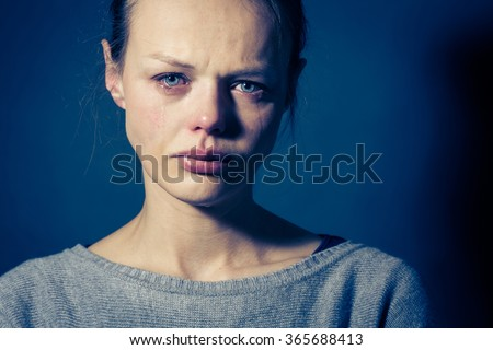 Young woman suffering from severe depression/anxiety/sadness, crying, tears coming from her eyes - stock photo