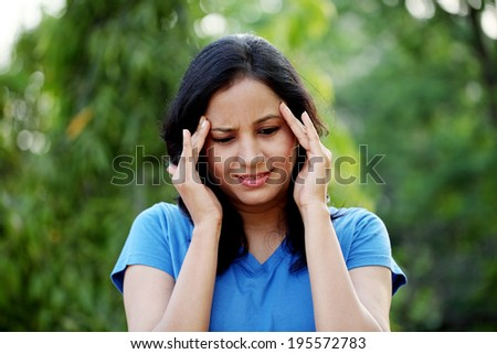 Young woman suffering with headache - stock photo