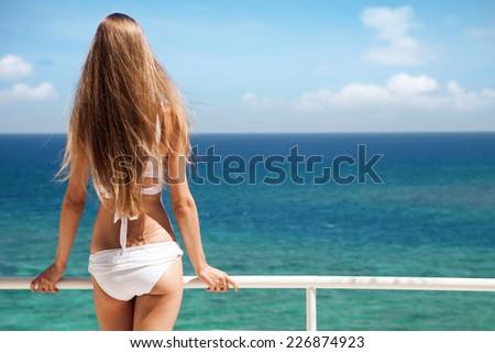 Young woman sunbathing. Nice sea view. - stock photo