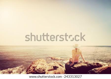 Young woman sunbathing on rocky beach. Vintage mood. Santorni Greece, Aegean sea - stock photo