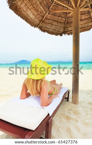 Young woman sunbathing on the chair near the ocean - stock photo