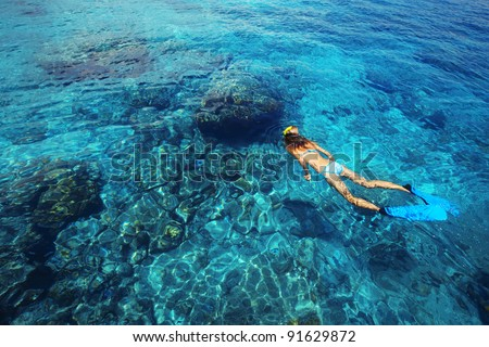 Young woman swimming in a clear tropical sea - stock photo