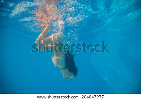 Young woman swimming undewater in the swimming pool - stock photo