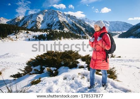 Young woman take a walk on winter mountain slope (Big Almaty Lake, Kazakhstan) - stock photo