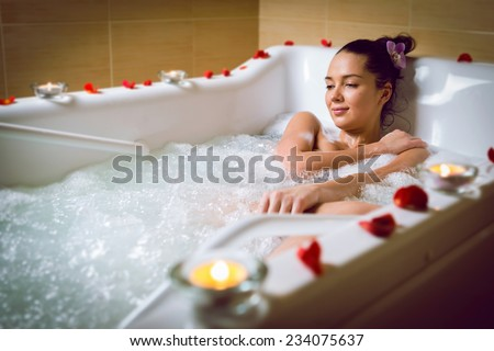 Young woman take bubble bath with candle.  - stock photo
