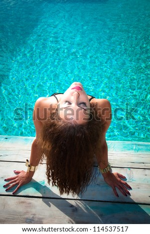 young woman take sunbathing by the pool, above view - stock photo