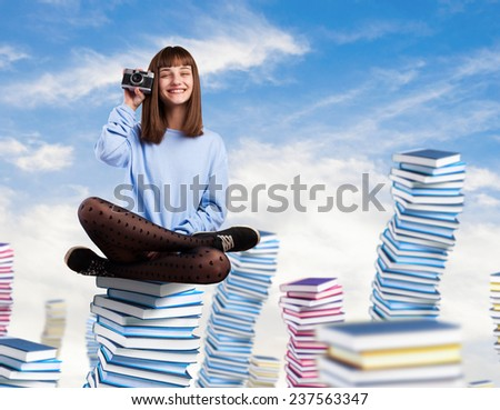 young woman taking a photo sitting on a high books tower - stock photo
