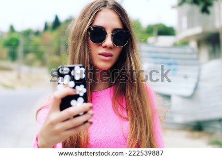 Young woman taking a selfie outdoors on sunny summer day. Photo toned style Instagram filters - stock photo