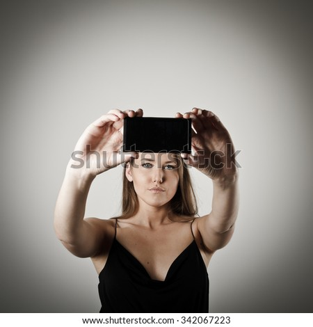 Young woman taking a selfie using her smartphone. - stock photo