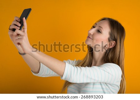 Young woman taking a selfie with mobile phone against orange background.  - stock photo