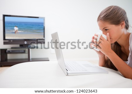 Young woman taking a sip of coffee while surfing the internet in the living room - stock photo