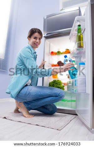 Young woman taking a water bottle from refrigerator and smiling at camera. - stock photo