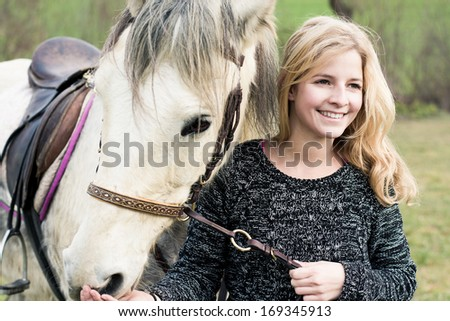 young woman taking care of her horse - stock photo