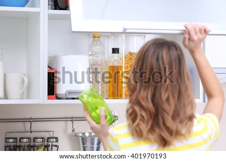 Young woman taking clean dishware in kitchen - stock photo