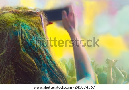 Young woman taking photo on mobile phone on holi color festival - stock photo
