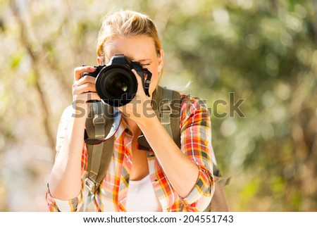 young woman taking photos in autumn forest with dslr - stock photo