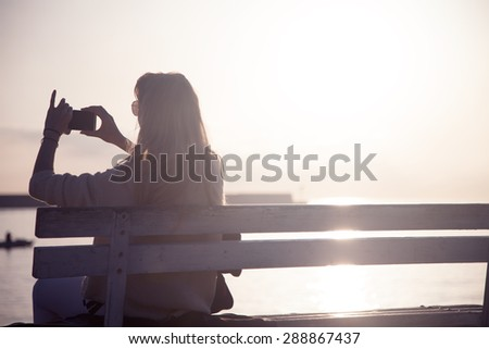 Young woman taking photos of beautiful sunrise over the sea. Outdoor shot. - stock photo