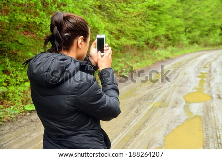 young woman taking photos with a mobile phone - stock photo