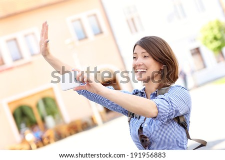 Young woman taking picture by the phone in the city - stock photo