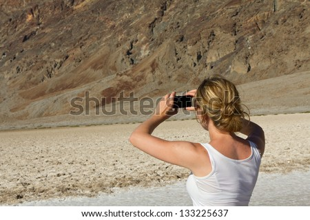 Young woman taking pictures of sand landscape in Death Valley - stock photo
