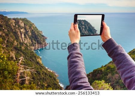 Young woman taking pictures on a tablet in mountains - stock photo