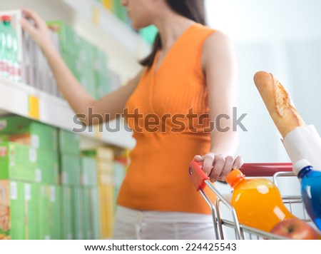 Young woman taking products from shelf at supermarket and holding a shopping cart. - stock photo