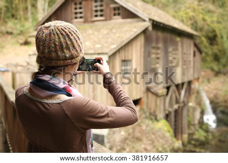 Young woman taking scenic photos with a cellphone.  - stock photo