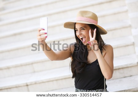 Young woman taking selfie outdoor - stock photo