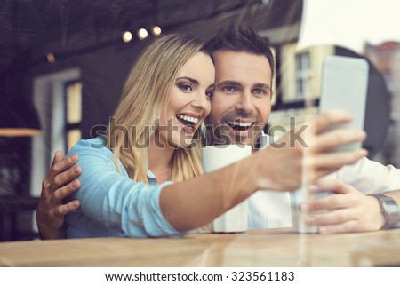 Young woman taking selfie with friend at cafe - stock photo
