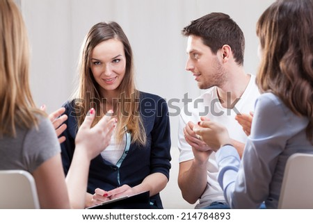 Young woman talking about her life on group therapy - stock photo