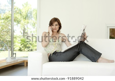 Young woman talking on a cell phone while reading a newspaper at home. - stock photo